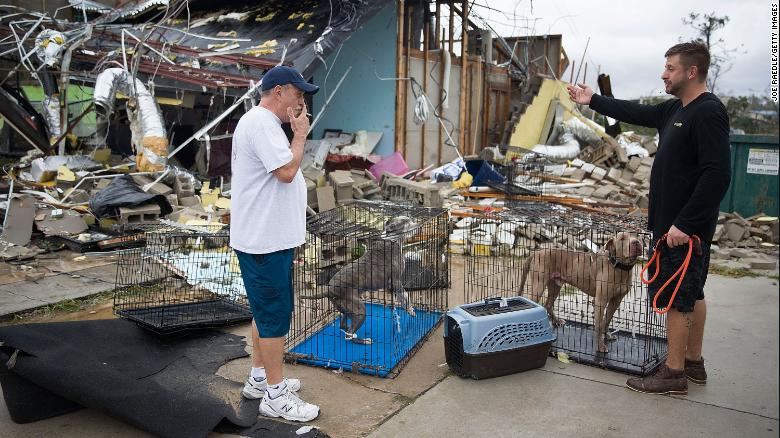 Residents rescue a couple of dogs after the storm destroyed several buildings in Panama City.