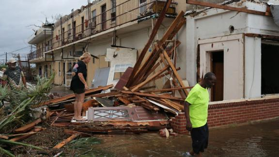 People make their way through a building's wreckage in Panama City on October 10.