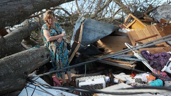 Kathy Coy stands among what is left of her home in Panama City. She said she was in the home when it was blown apart and is thankful to be alive.