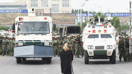 A woman stands in front of police and riot vehicles on July 7, 2009 in Urumqi, the capital of Xinjiang.