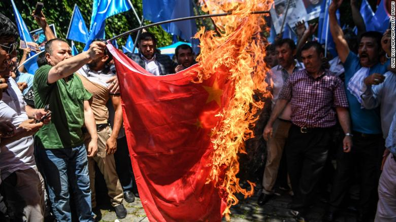 Protesters burn a Chinese flag during a demonstration to denounce China's treatment of Uyghurs in front of the Chinese consulate in Istanbul, on July 5, 2018.