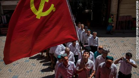 Ethnic Uyghur members of the Communist Party of China carry a flag as they take part in an organized tour on June 30, 2017 in the old town of Kashgar, in the far western Xinjiang province, China.