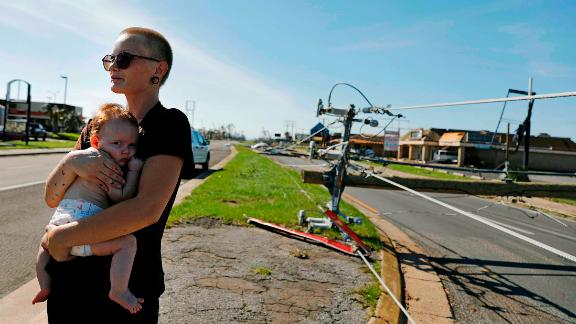 Kylie Strampe holds her 4-month-old daughter, Lola, while surveying the damage in Callaway, Florida, on October 11.