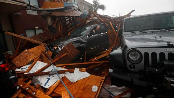 A storm chaser tries to get equipment out of his vehicle amid the wreckage in Panama City Beach.