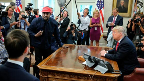 """Rapper Kanye West stands up during his Oval Office meeting with Trump in October 2018. West and football legend Jim Brown <a href=""""https://www.cnn.com/2018/10/11/politics/kanye-west-donald-trump-white-house-chicago/index.html"""" target=""""_blank"""">had been invited for a working lunch</a> to discuss topics such as urban revitalization, workforce training programs and how best to address crime in Chicago."""