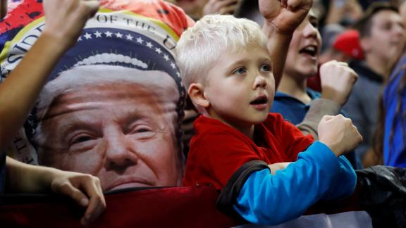 A child watches as President Donald Trump holds a campaign rally in Council Bluffs, Iowa, October 9, 2018.