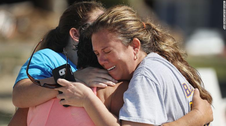 Elizabeth Hanson, right, and daughter Emaly hug their neighbor Cindy Clark in Mexico Beach.
