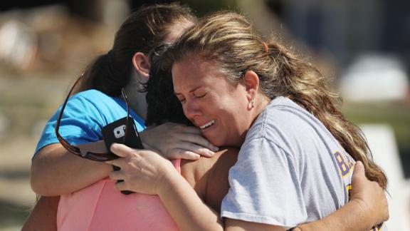 Elizabeth Hanson, right, and her daughter Emaly hug their neighbor Cindy Clark on October 11. The hurricane heavily damaged their homes in Mexico Beach.