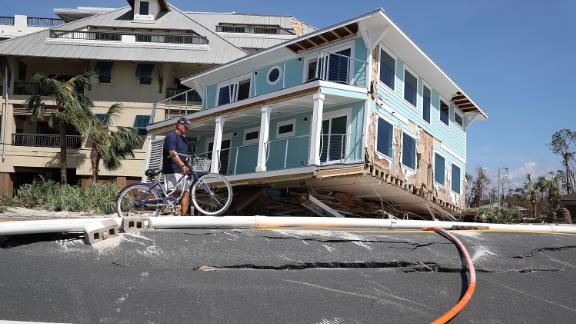 Tom Bailey walks his bike past a home that was carried across a road and slammed up against a condo complex in Mexico Beach.