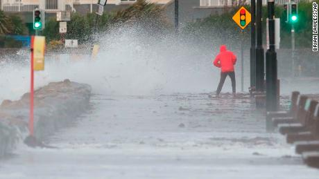 A man avoids the waves at Salthill promenade, County Galway, Ireland, during Storm Callum.