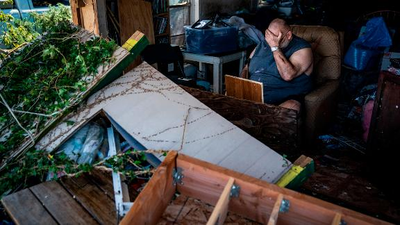 Benny Hobson sits in his recliner on Thursday, October 11, after losing the front wall of his house in Panama City, Florida.