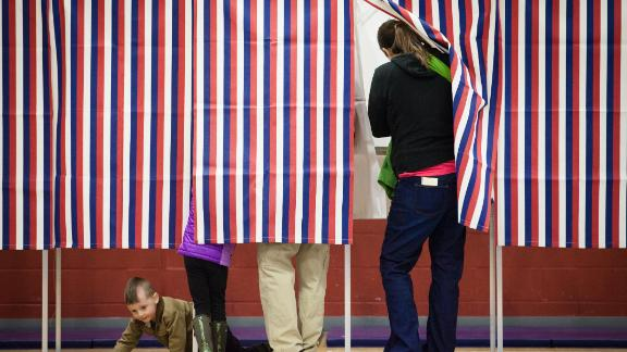 CONCORD, NH - FEBRUARY 09: 3 year old Simon Desmarais crawls beneath voting booths as his parents Ashley Grover (R) and Andrew Desmarais cast their votes on February 9, 2016 at Broken Ground School in Concord, NH. Voters throughout the state are heading to the polls as the New Hampshire Primary, also known as the first-in-the-nation primary, continues the process of selecting the next president of the United States. (Photo by Matthew Cavanaugh/Getty Images)