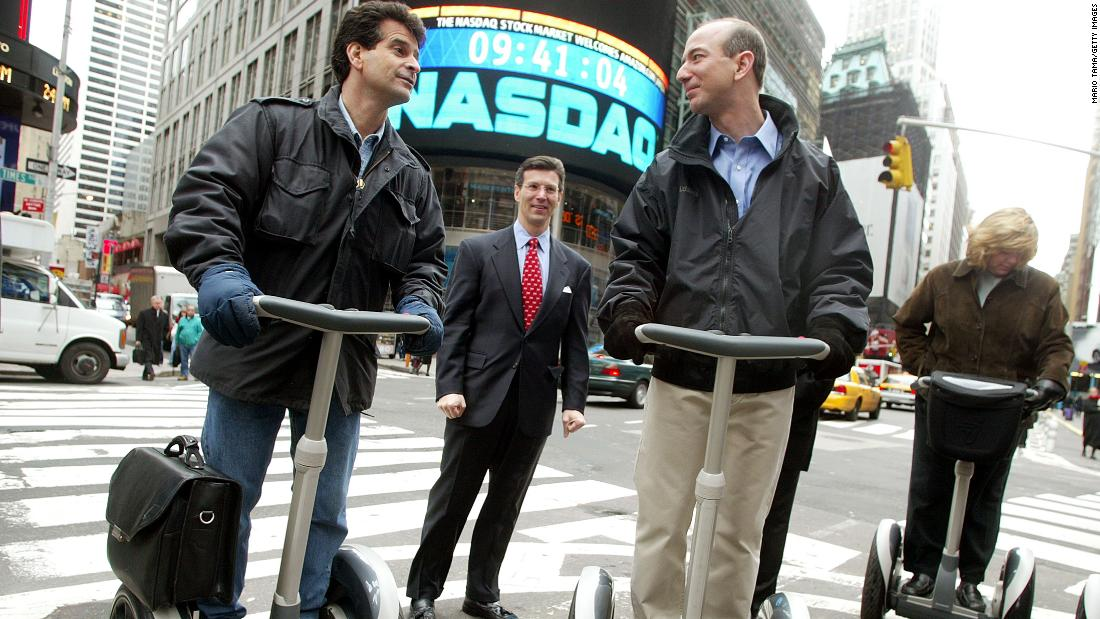 Amazon CEO Jeff Bezos stands on a Segway PT with Dean Kamen and NASDAQ Vice Chairman David Weild, center, after opening the NASDAQ on Nov. 18, 2002, the same day the device went on sale to the public. (Photo by Mario Tama/Getty Images)