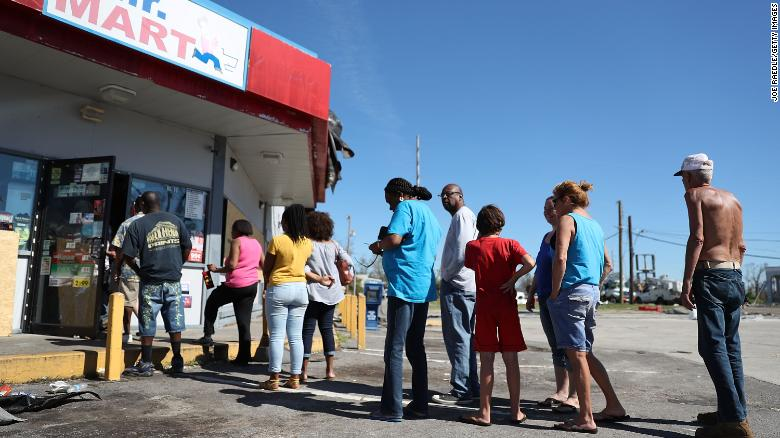 Residents line up outside a Panama City convenience store after Michael destroyed much of the city.