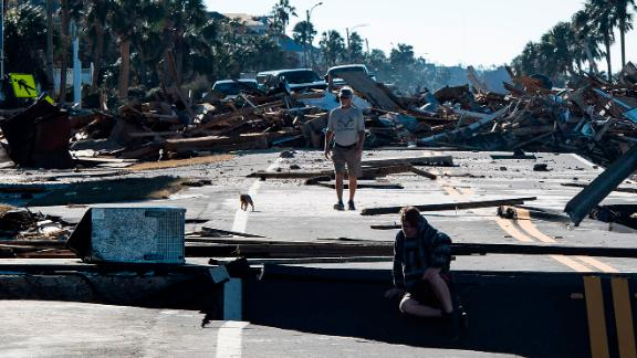 Mexico Beach residents make their way across a washed-out road on Friday, October 12.
