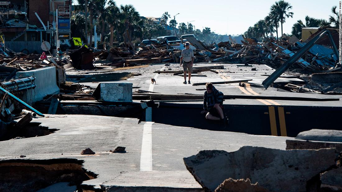Residents make their way across a washed-out road on Friday, October 12, in Mexico Beach, Florida, a resort town that's been ground zero of the catastrophic hurricane's destruction.