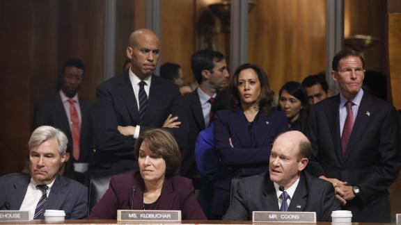 Senator Chris Coons, a Democrat from Delaware, bottom right, speaks as Senator Amy Klobuchar, a Democrat from Minnesota, and Senator Sheldon Whitehouse, a Democrat from Rhode Island, bottom left, listen during a Senate Judiciary Committee markup hearing in Washington, D.C., U.S., on Friday, Sept. 28, 2018. A Senate Judiciary Committee vote onBrett Kavanaugh'sSupreme Court nomination was held up by last-minute wrangling Friday by members of the panel, as Republicans and Democrats continued to spar over sexual assault allegations against the nominee. Photographer: Aaron P. Bernstein/Bloomberg via Getty Images