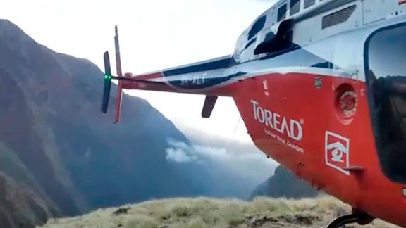 In this grab taken from video provided by SIMRIK AIR, a helicopter lands close to a storm site after searching for missing mountaineers on the Gurja Himal mountain, in Nepal, Saturday, Oct. 13, 2018. Seven people, including South Korean climbers, were killed and two more are missing on Gurja Himal mountain after a strong storm swept through their base camp, Nepalese police said Saturday. (SIMRIK AIR via AP)