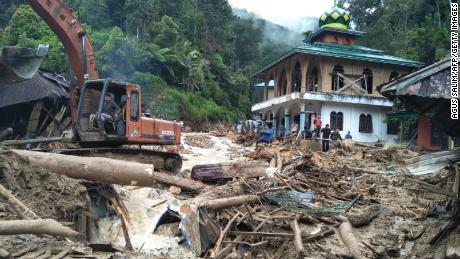 Rescuers remove debris after flash flooding Friday in North Sumatra, Indonesia.