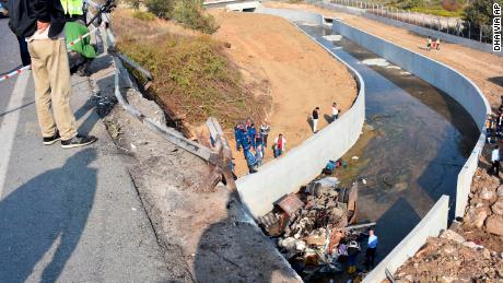 Rescue workers inspect an overturned truck in Izmir province.