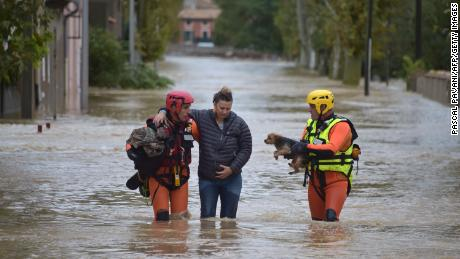 Firefighters help a resident in Trebes, near Carcassonne, southern France.