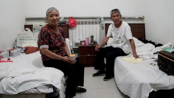 Cao Ruizhe and her huband, Yao Shuping, sit in their rented hotel room, awaiting her next cancer treatment.