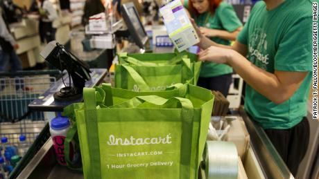 InstaCart employees fulfill orders for delivery at the new Whole Foods Market Inc. store in downtown Los Angeles, California, U.S., on Monday, Nov. 9, 2015. Located beneath the recently opened Eighth & Grand residences, the 41,000-square-foot store features a juice bar, fresh poke, expanded vegan options in all departments, a coffee bar (with cold brew on tap), more than 1,000 hand-picked wines, home delivery via Instacart and bar-restaurant The Eight Bar.