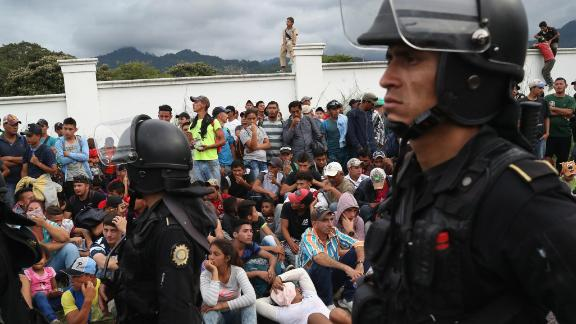 A caravan of Honduran migrants pauses at a Guatemalan police checkpoint after crossing the border from Honduras on October 15.