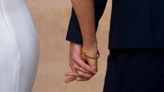 The Duke and Duchess hold hands as they walk inside after posing for a photo in Sydney.