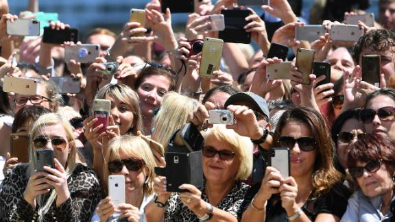 Well-wishers take photos of Harry and Meghan outside the Sydney Opera House.