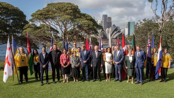 Harry and Meghan pose for a group photo at Admiralty House in Sydney with Cosgrove (front row, sixth from left); his wife, Lynn Cosgrove (fourth from left); and representatives of countries participating in the Invictus Games.