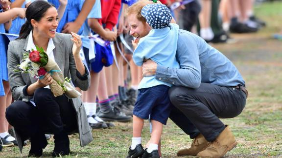 Harry and Meghan are greeted by 5-year-old Luke Vincent as they arrive on Wednesday, October 17, in Dubbo, Australia.