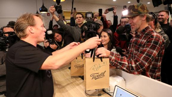 Canopy Growth CEO Bruce Linton hands Ian Power, who is first in line to purchase the first legal recreational marijuana after midnight, his purchases at a Tweed retail store in St John