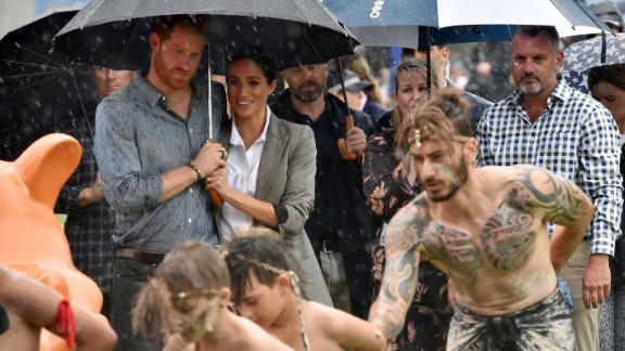 Harry and Meghan watch aboriginal dances from under an umbrella at Victoria Park in Dubbo.