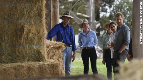 Prince Harry and wife Meghan chat with farmers Scott Woodley, his daughter Laura and wife Elaine during a visit to their drought-affected farm in Dubbo.