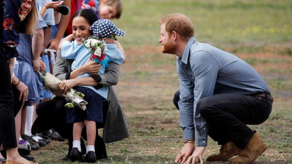 Meghan, Duchess of Sussex, gets a hug and a bouquet of flowers from 5-year-old Luke Vincent.