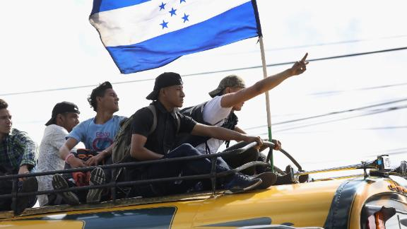 Migrants display the flag of Honduras while on a caravan of migrants en route to the Mexican border on Thursday in Guatemala City. The caravan of thousands of Central Americans, most from Honduras, hopes to eventually reach the United States. President Donald Trump has threatened to cancel the recent trade deal with Mexico and withhold aid to Central American countries if the caravan isn