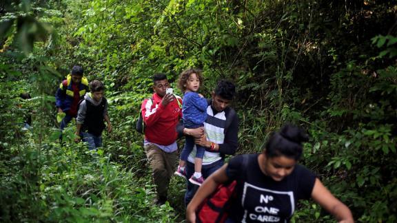 Honduran migrants hike in the forest after crossing the Lempa River, on the border between Honduras and Guatemala, to join the caravan on Thursday.