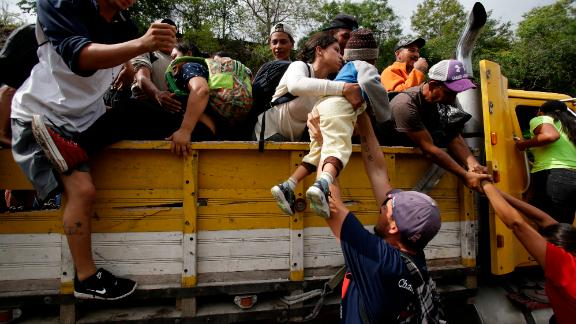Honduran migrants climb into the bed of a truck in Zacapa, Guatemala, on Wednesday, October 17, 2018.