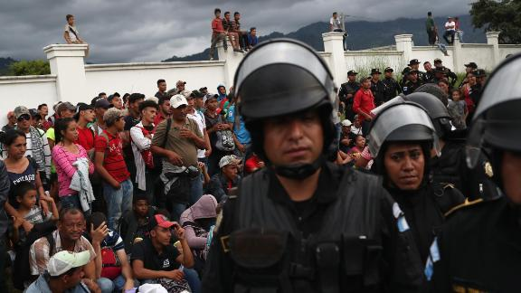 The caravan pauses at a Guatemalan police checkpoint after crossing the border from Honduras on Monday.