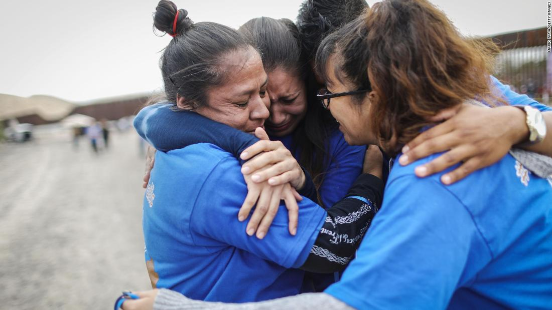 Iliana Nieves, left, hugs family members after she was briefly reunited with her mother on the other side of the wall at the Hugs Not Walls event on the US-Mexico border in Sunland Park, New Mexico, on Saturday, October 13. More than 200 families with mixed immigration status living in the United States were allowed to reunify with relatives in Mexico for three minutes after Border Patrol briefly opened the border wall to allow the reunions.