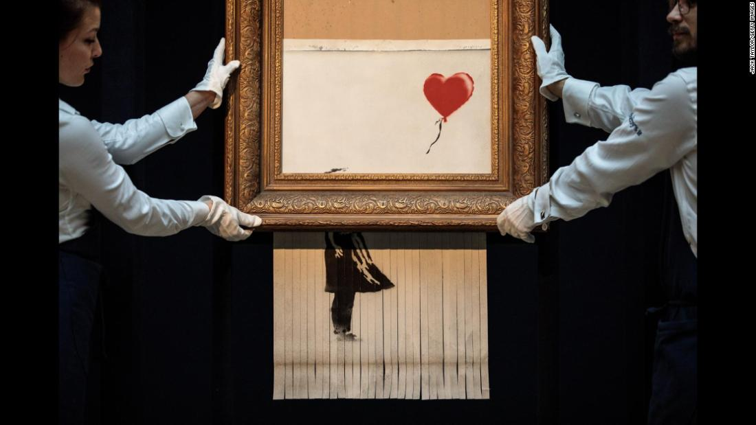 "Sotheby's employees pose with ""Love is in the Bin"" by British artist Banksy during a media preview at Sotheby's auction house in London on Friday, October 12. The work was renamed from ""Girl with Balloon"" after it <a href=""https://www.cnn.com/style/article/banksy-painting-self-destructs-auction-trnd/index.html"" target=""_blank"">shredded through the bottom of the frame as it was sold</a> during Sotheby's Contemporary Art Sale on October 5."