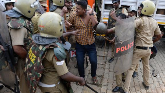 Police take a Hindu activist into custody as protesters rally against the Supreme Court verdict.