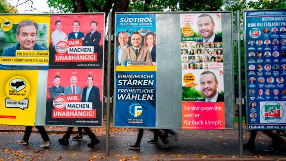 People pass behind election posters in Bolzano, Italy on October 15, 2018.