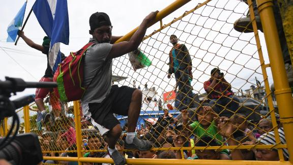 Honduran migrants heading in a caravan to the United States crowd the gate of the Guatemala-Mexico border bridge in Ciudad Hidalgo, Mexico, on Friday, October 19.