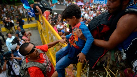A child is lifted over the border fence as thousands of Honduran migrants rush across the border toward Mexico, in Tecun Uman, Guatemala, Friday, October 19.