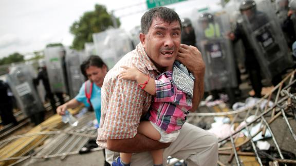 A Honduran man protects his child after fellow migrants, part of a caravan trying to reach the United States, stormed a border checkpoint in Guatemala, in Ciudad Hidalgo, Mexico, Friday, October 19.
