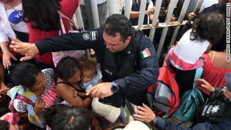 Mexican Federal Police Officers Allow Women And Children Taking Part In A Caravan Of Honduran