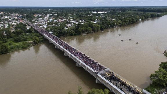An aerial view shows a Honduran migrant caravan heading to the United States as it is stopped at a border barrier on the Guatemala-Mexico international bridge in Ciudad Hidalgo, Mexico, on Friday, October 19.