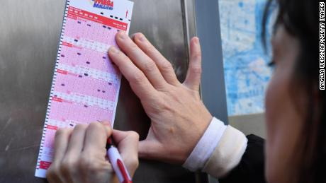 A woman fills out a Mega Millions lottery ticket in New York on Friday.